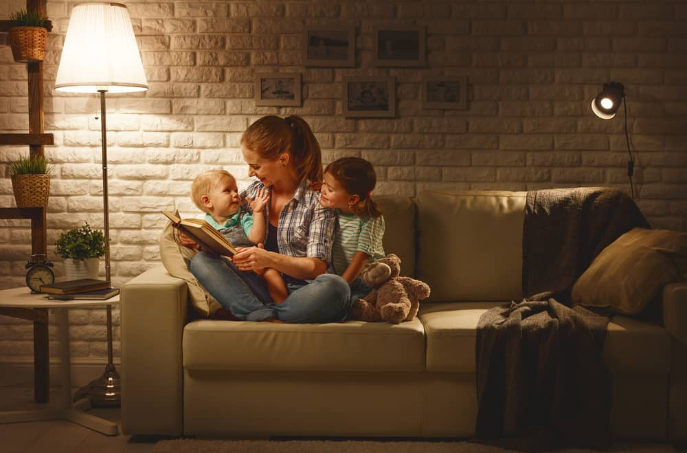 Mom reading kids a book with a lamp on
